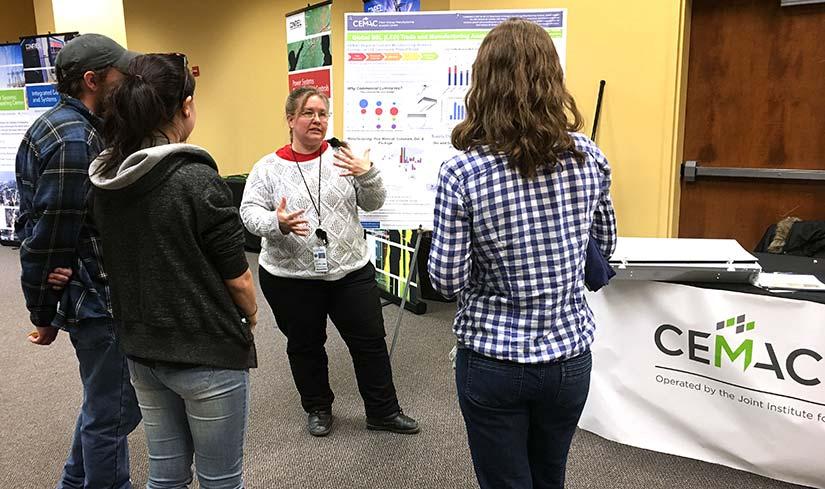 Foto de un grupo de tres personas de pie y escuchando a una mujer presente frente a un cartel. El cartel de la CEMAC está en primer plano.