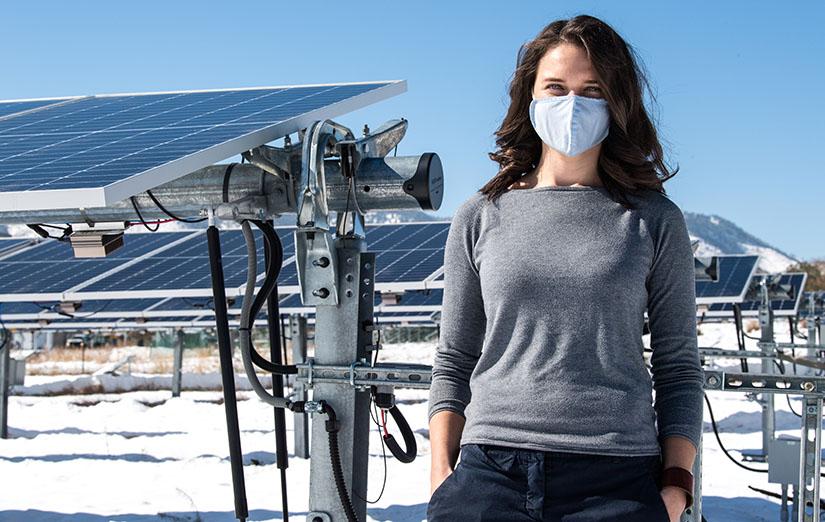 Una mujer se encuentra junto a un campo fotovoltaico en NREL.